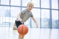 Schoolboy playing basketball in gym class - WESTF24127