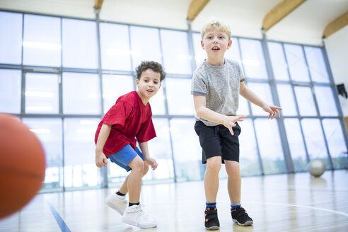 Two schoolboys playing basketball in gym class - WESTF24130