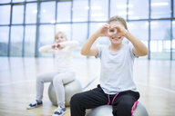 Portrait of smiling schoolgirls sitting on gym balls in gym class - WESTF24133