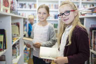 Portrait of two smiling schoolgirls with books in school library - WESTF24136