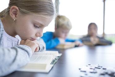 Schoolgirl reading book on table in school break room - WESTF24142