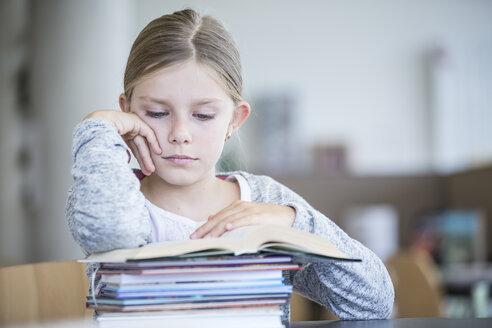 Schoolgirl reading book on table in school - WESTF24145