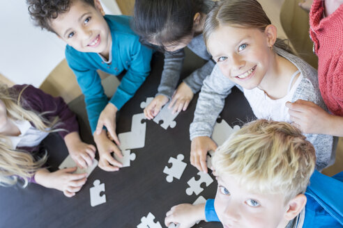 Portrait of smiling pupils playing jigsaw puzzle in school together - WESTF24151