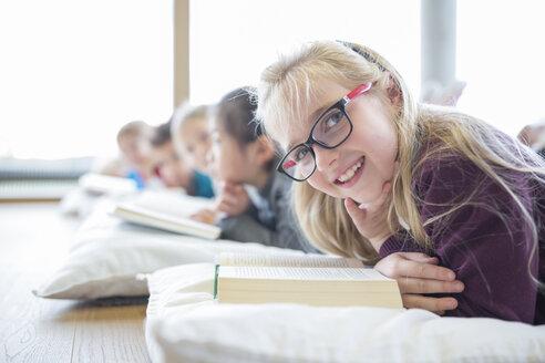 Portrait of smiling schoolgirl lying on the floor with classmates reading book in school break room - WESTF24160