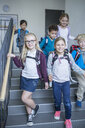Happy pupils on staircase leaving school - WESTF24169