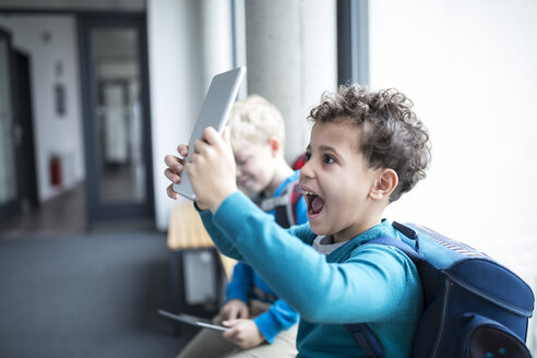Happy schoolboy holding up tablet on corridor in school - WESTF24172