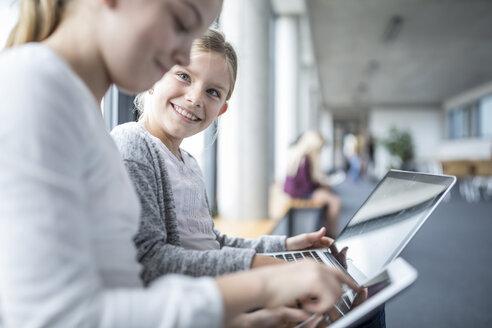 Happy schoolgirls with laptop and tablet on school corridor - WESTF24175