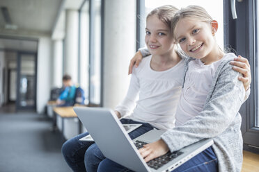 Portrait of two smiling schoolgirls with laptop and tablet embracing - WESTF24178