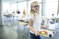 Portrait of smiling schoolgirl carrying tray in school canteen - WESTF24199