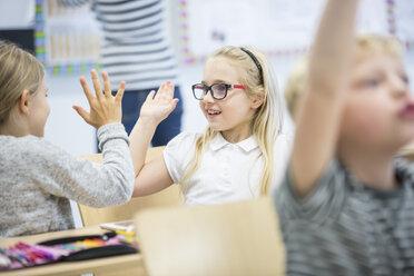 Happy schoolgirls high fiving in class - WESTF24208