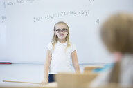 Schoolgirl standing at whiteboard with formula in class - WESTF24211