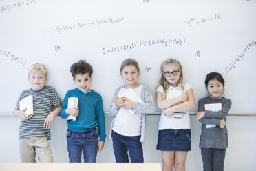 Portrait of smiling pupils standing at whiteboard with formulas in class - WESTF24214