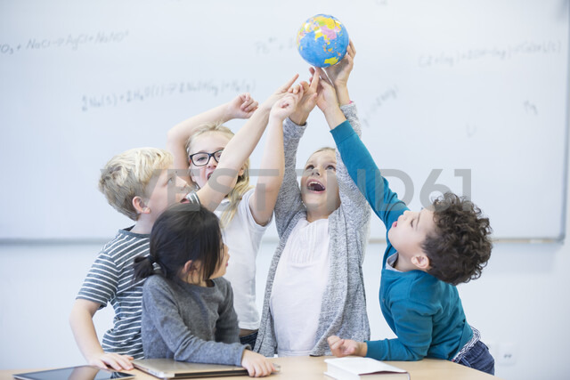 Happy pupils holding globe together in class - WESTF24220