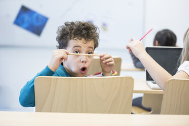 Schoolboy in class staring at pencil - WESTF24226