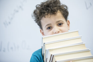 Portrait of schoolboy carrying books in class - WESTF24229