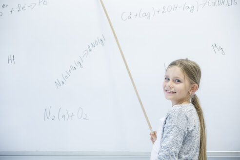 Smiling schoolgirl explaining formula at whiteboard in class - WESTF24232