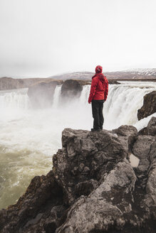 Iceland, man standing at Godafoss waterfall - KKAF01034