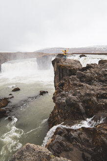 Iceland, woman standing at Godafoss waterfall with raised arms - KKAF01037