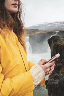 Iceland, woman with cell phone at Godafoss waterfall - KKAF01043
