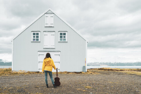 Iceland, woman with guitar standing at lonely house - KKAF01046