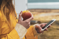 Iceland, close-up of woman holding cell phone and apple - KKAF01052