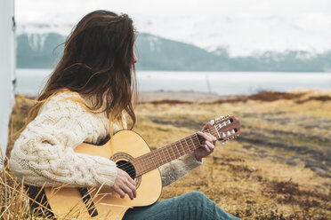Iceland, woman sitting in rural landscape playing guitar - KKAF01055