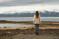 Iceland, woman standing at lakeside - KKAF01058