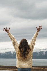 Iceland, woman standing at lakeside with raised arms - KKAF01061