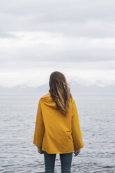 Iceland, woman standing at the sea - KKAF01064