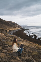 Iceland, woman using laptop at the coast - KKAF01073