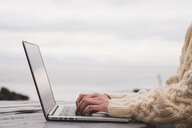 Iceland, woman using laptop on wooden table - KKAF01076