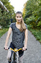 Portrait of sportive young woman with bicycle in a park - MMIF00080