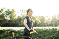 Sportive young woman with bicycle in nature - MMIF00083