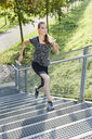 Young woman running on stairs in a park - MMIF00092