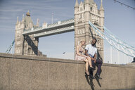Young couple sitting on wall, smiling, Tower Bridge in background, London, England, UK - ISF05794