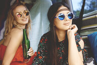Two young boho women wearing sunglasses in recreational van - ISF05812