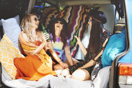 Three young boho women laughing in recreational van - ISF05815