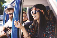 Young boho adults looking out and playing guitar in recreational van doorway - ISF05818