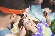 Over shoulder view of young man putting headband on young woman lying on picnic blanket - ISF05821