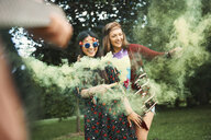 Young boho women dancing with green smoke flare  at festival - ISF05833