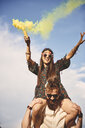 Young boho woman holding yellow smoke flare on boyfriend's shoulders at festival - ISF05836