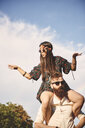 Young boho woman dancing on boyfriend's shoulders at festival - ISF05854