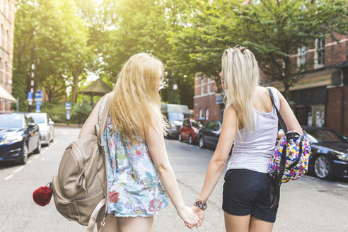 Two female friends, walking outdoors, holding hands, rear view - ISF05860