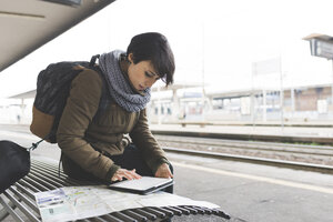 Female backpacker looking at map and digital tablet on railway platform - ISF05944