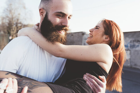 Bearded man carrying smiling woman in arms - ISF05983