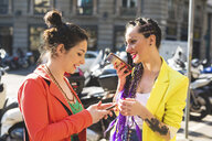 Women in city break using mobile phone, Milan, Italy - ISF05992