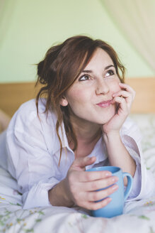 Young woman on bed with coffee cup, looking up - ISF06022