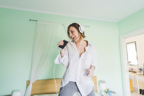 Young woman on bed wearing headphones and singing into smartphone - ISF06025