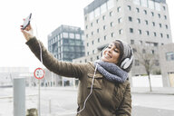 Mid adult woman taking smartphone selfie in city - ISF06079