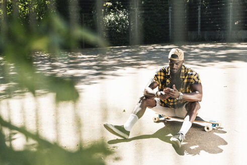 Cool young man in skate park, using smartphone - UUF13839